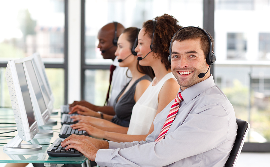 Smiling businessman working in a call center with his colleagues